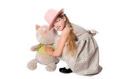 A menina agradável joga com o brinquedo macio do gato Fotografia de Stock Royalty Free