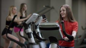 A menina agradável na camisa vermelha vigorosamente trabalha na bicicleta de exercício e fala com seu telefone no gym novo contra vídeos de arquivo