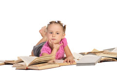 Menina agradável que encontra-se na pilha dos livros imagens de stock