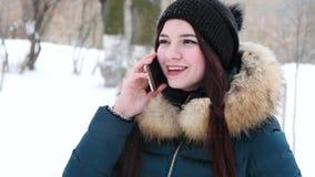 Menina agradável que fala pelo telefone celular no parque do inverno video estoque