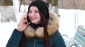 Menina agradável que fala pelo telefone celular no parque do inverno filme