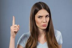 Menina agradável que mantém seu dedo Fotos de Stock Royalty Free
