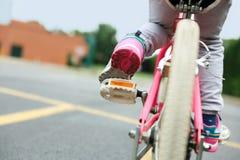 Menina agradável que monta sua bicicleta em uma estrada Imagem de Stock Royalty Free