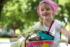 Menina agradável que monta sua bicicleta em uma estrada Fotografia de Stock Royalty Free