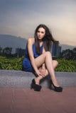 Menina agradável que senta-se atrás do por do sol Foto de Stock Royalty Free