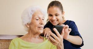 A menina ajuda a avó que usa o telefone celular e a tecnologia Imagem de Stock Royalty Free