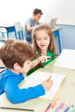 A menina ajuda um menino na sala de aula foto de stock royalty free