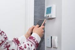 A menina ajusta e regula a temperatura ambiente com o telefone esperto na parede do interruptor foto de stock