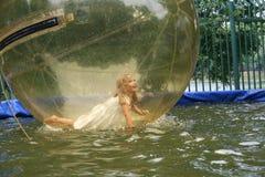 Menina alegre ao úmido em uma bola transparente Fotografia de Stock Royalty Free