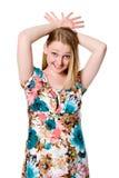 A menina alegre bonita com dedos espalhou sobre sua cabeça. Fotos de Stock Royalty Free
