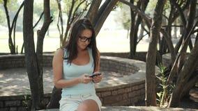 Menina alegre bonita com Smartphone que senta-se em um parque em um banco em Sunny Day, conceito em linha da compra video estoque