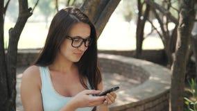 Menina alegre bonita com Smartphone que senta-se em um parque em um banco em Sunny Day, conceito em linha da compra Imagem de Stock