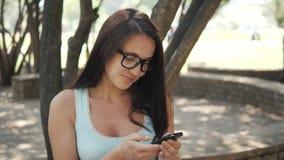 Menina alegre bonita com Smartphone que senta-se em um parque em um banco em Sunny Day, conceito em linha da compra Fotografia de Stock