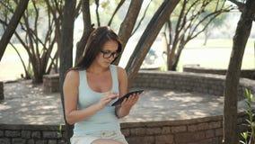 Menina alegre bonita com um PC da tabuleta que senta-se em um parque em um banco em Sunny Day, conceito em linha da compra Fotografia de Stock