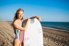 Menina alegre bonita do surfista na praia no por do sol imagem de stock royalty free