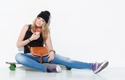 A menina alegre bonita nova da forma nas calças de brim, sapatilhas, chapéu que senta-se em um longboard com um saco do vintage e Foto de Stock Royalty Free