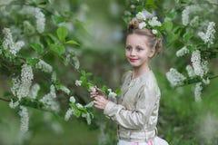 Menina alegre bonito no jardim florescido da cereja-?rvore imagens de stock