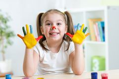 A menina alegre bonito que mostra a pintou as mãos Imagens de Stock Royalty Free