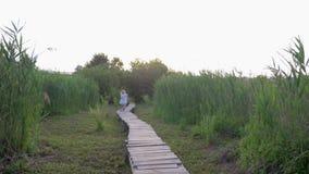 Menina alegre com a atualização e a corrida do jogo do menino do amigo na ponte de madeira na natureza entre juncos verdes filme