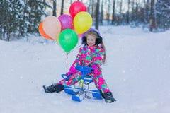 A menina alegre com cabelo de fluxo longo em macacões coloridos vai da montanha com bolas coloridas Foto de Stock