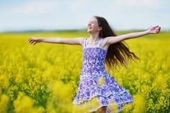 Menina alegre com a festão da flor no prado amarelo da colza Imagem de Stock Royalty Free