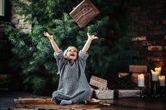 A menina alegre com o cabelo encaracolado louro que veste uma camiseta morna joga acima uma caixa de presente ao sentar-se em um  fotos de stock royalty free
