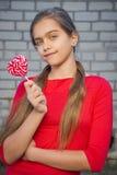 Menina alegre com um doce, Fotos de Stock Royalty Free