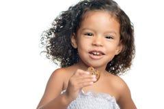 Menina alegre com um penteado afro que come uma cookie do chocolate Fotografia de Stock Royalty Free