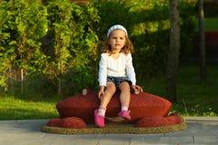 Menina alegre da criança no campo de jogos ensolarado do verão no parque Modelo branco da camisa de t Fotografia de Stock Royalty Free
