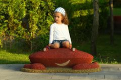 Menina alegre da criança no campo de jogos ensolarado do verão no parque Modelo branco da camisa de t Imagem de Stock