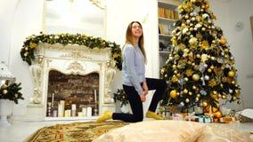 A menina alegre decora a árvore de Natal e prepara-se por feriados no assoalho na sala de visitas festiva decorada na noite filme