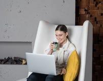 Menina alegre do moderno que tem a chamada video em linha através do rede-livro portátil durante a ruptura de trabalho foto de stock royalty free
