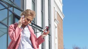 Menina alegre do negócio no telefone que discute matérias pessoais vídeos de arquivo
