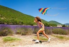Menina alegre do preteen que corre com papagaio do arco-íris fotos de stock