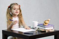 A menina olha feliz no quadro, sentando-se na tabela na imagem do escritor Fotos de Stock