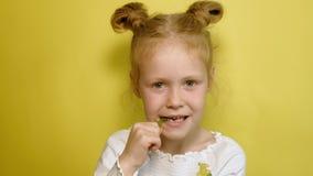 Menina alegre em um fundo amarelo com geleia da cor Retrato do close up filme