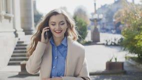 A menina alegre em um revestimento branco vai e fala em um smartphone vídeos de arquivo