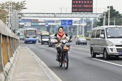 Menina alegre em uma bicicleta elétrica na estrada, Guangzhou, China Imagens de Stock Royalty Free