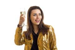 A menina alegre encantador no revestimento dourado aumenta um vidro em no sua mão e riso Fotografia de Stock