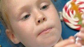 A menina alegre encontra-se em um fundo azul com doces Retrato do close up vídeos de arquivo
