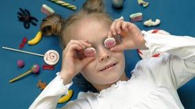 A menina alegre encontra-se em um fundo azul com doces Retrato do close up video estoque