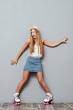 Menina alegre engraçada nos patins do chapéu e de rolo que têm o divertimento Imagens de Stock