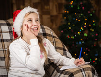 A menina alegre escreve uma letra a Santa Claus Fotos de Stock Royalty Free