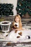 A menina alegre está jogando com os cones no fundo da árvore de Natal Fotos de Stock Royalty Free