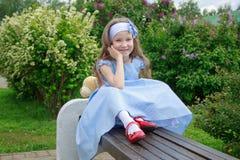 A menina alegre está sentando-se em um banco de madeira no parque Foto de Stock