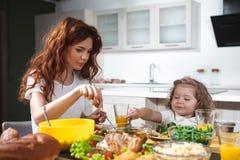 A menina alegre está tendo o almoço com sua mamã foto de stock royalty free
