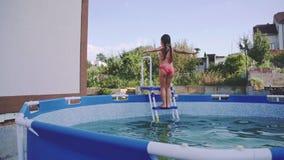A menina alegre está tendo o divertimento na piscina do ar livre Fps do movimento lento 240 A criança é de salto e de jogo dentro vídeos de arquivo