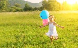 Menina alegre feliz que joga e que tem o divertimento com os balões no verão Imagens de Stock Royalty Free