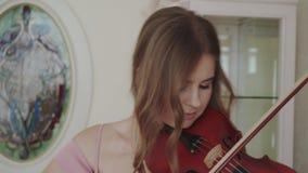 A menina alegre joga no violino com entusiasmo e harmonia na câmera video estoque