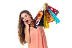 A menina alegre mantém uma mão perto da boca e nos segundos sacos brilhantes diferentes aumentados isolados no fundo branco Imagem de Stock Royalty Free